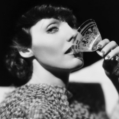 circa 1930:  American actress Adrienne Ames (1909-1947) dressed in a chiffon tiered dress, drinks from a cocktail glass.  (Photo via John Kobal Foundation/Getty Images)